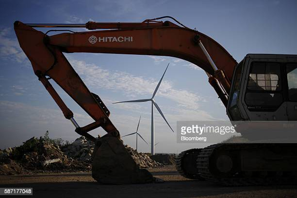 A Hitachi Ltd construction vehicle stands in front of wind turbines operated by Pattern Energy Group Inc at the Amazon Wind Farm Fowler Ridge in...