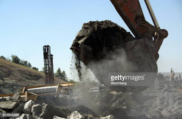 A Hitachi Ltd trackhoe excavator moves rocks during highway construction between US Route 23 and US Route 52 near Portsmouth Ohio US on July 26 2017...