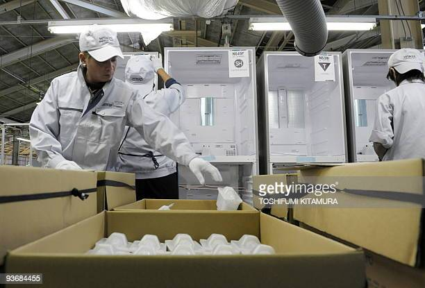 Hitachi workers put together parts on an assemble line for refrigerators at the Hitachi Appliances Tochigi Works plant in the town of Ohira in...