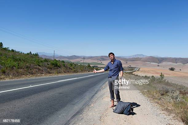 hitchhiker on side of road - hitchhiking stock pictures, royalty-free photos & images