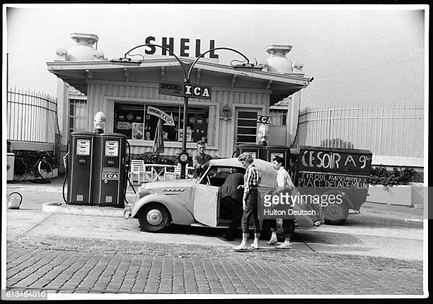 Hitchhikers Irene Mayo and Gillian Webb stop at a petrol station with some men who fill the car with gas. They are hitchhiking to the French Riviera...