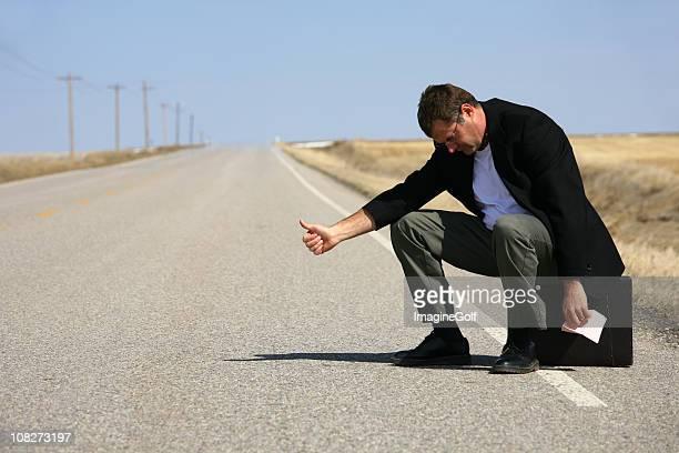 Hitchhiking Caucasian Businessman Holding Pink Slip