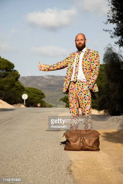 hitchhiking man wearing suit with colourful polka-dots standing at roadside with travelling bag - multi colored suit stock pictures, royalty-free photos & images