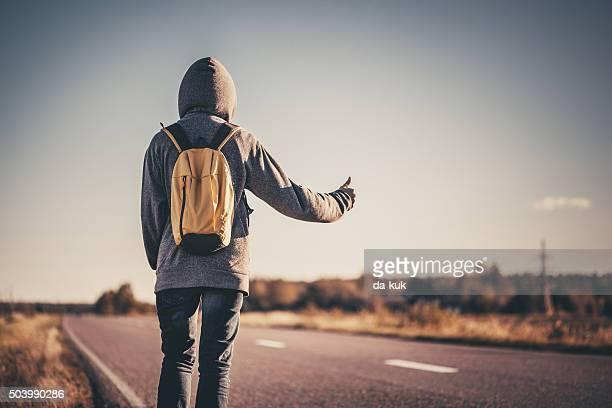 L'autostop traveler tentando di fermare l'auto sulla strada