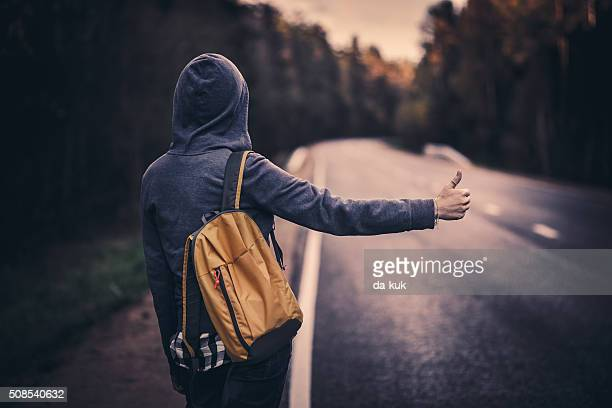 Hitchhiking traveler trying to stop the car on road