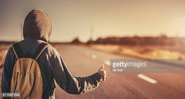 hitchhiking traveler trying to stop the car on road - hitchhiking stock pictures, royalty-free photos & images