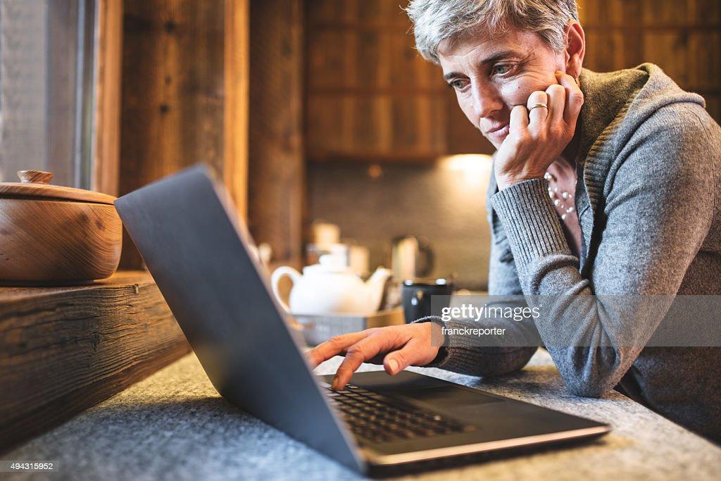 hitech senior woman surfing on the kitchen : Stock Photo
