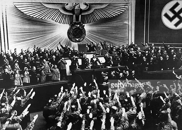 Hitler accepts an ovation from the Reichstag on March 13 1938 after announcing the annexation of Austria or Anschluss German troops had occupied the...