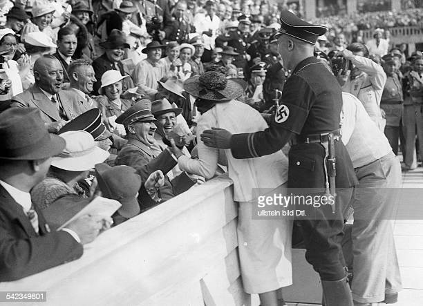 Hitler Adolf Politician NSDAP Germany *20041889 Adolf Hitler laughing in the audience in the olympic stadium while a female Fan is asking for a...
