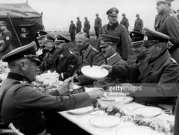 Hitler Adolf Politician NSDAP Germany *20041889 Adolf Hitler eating in a field kitchen with officers of the German Wehrmacht near Karlsbad besides...