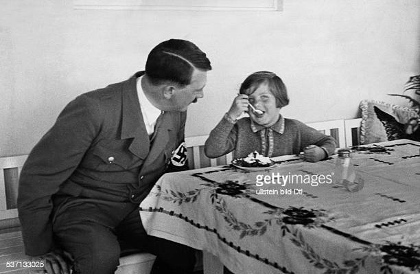 Hitler Adolf Politician NSDAP Germany Cwith a girl eating cake on the terrace of House Wachenfeld in the Obersalzberg region near Berchtesgaden 1939...