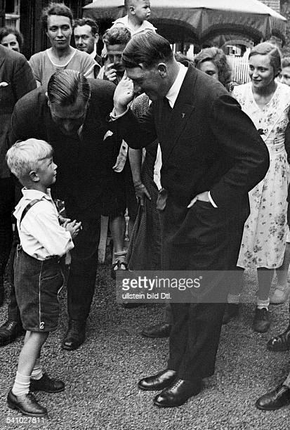 Hitler Adolf Politician NSDAP Germany*20041889 greeting a boy in lederhosen with the Hitler salute on the löeft Hitler's personal adjutant Wilhelm...