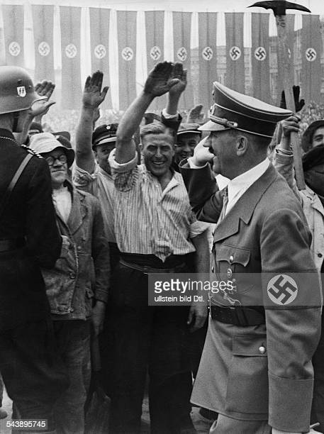 Hitler Adolf Politician NSDAP Germany*20041889 greets the workers during the groundbreaking of the German ' Haus des Deutschen Fremdenverkehrs '...