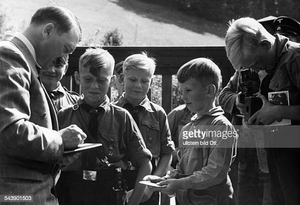 Hitler Adolf Politician NSDAP Germany*20041889 Hitler gives autographes to boys of the Hitler youth at the Berghof /Obersalzberg undated Photographer...