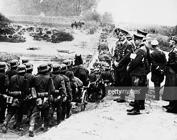 Hitler and other high German officers watch a long line of Nazi soldiers marching through the mud of Poland after Germany attacked Poland in the...