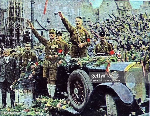 Hitler attending a Nazi Party rally in Nuremberg standing to salute in his car Julius Streicher in Grey suit stands to the left of the picture while...
