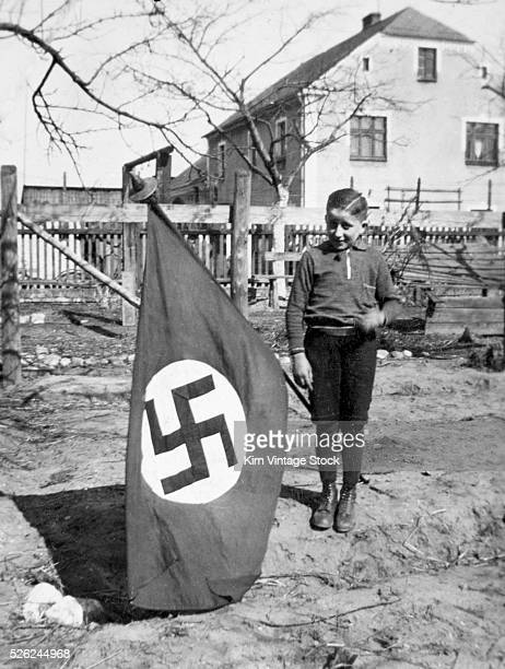 A Hitler youth boy poses with Nazi flag ca 1938