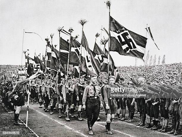 'Hitler Youth rally on National Socialist Party Day saluting and carrying Nazi flags '