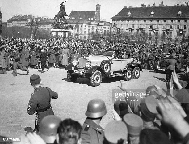 Hitler's car passes through a triumphant crowd assembled near the Hofburg in Vienna to celebrate the Anschluss in March 1938