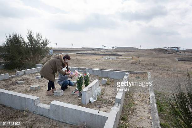 Hitomi Aizawa and Minami Fukumura offer flowers to the place where their uncle's house used to stand on March 11 2016 in Sendai Japan Today marks the...
