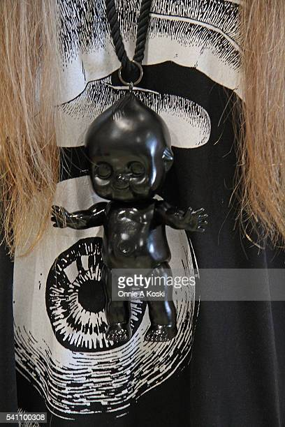 Hitomi is wearing an ME gothic shirt an oversized black Kewpie Doll necklace Paris Miki eyeglasses a CA4LA hat a clear pvc wrist cuff a MALICIOUS x...