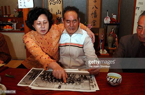 Hitomi Soga and her father Shigeru watch the photo taken at the graduation ceremony of her elementary school on October 22 2002 in Mano Niigata Japan...
