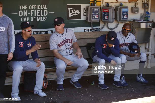 Hitting Coach Alex Cintron and Manager AJ Hinch of the Houston Astros talk in the dugout during the game against the Oakland Athletics at the...