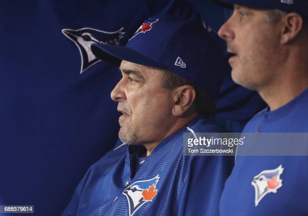 Hitting coach Brook Jacoby of the Toronto Blue Jays looks on from the dugout as he sits beside quality control coach Derek Shelton during MLB game...