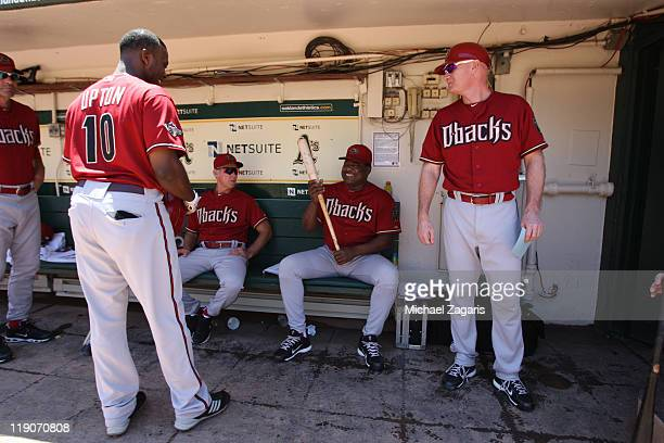 Hitting coach Don Baylor of the Arizona Diamondbacks rubs the bat of Justin Upton for good luck before the game against the Oakland Athletics at the...