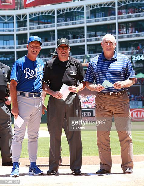 Hitting coach George Brett of the Kansas City Royals umpire Dale Scott and Nolan Ryan CEO of the Texas Rangers exchange lineup cards marking 20 years...