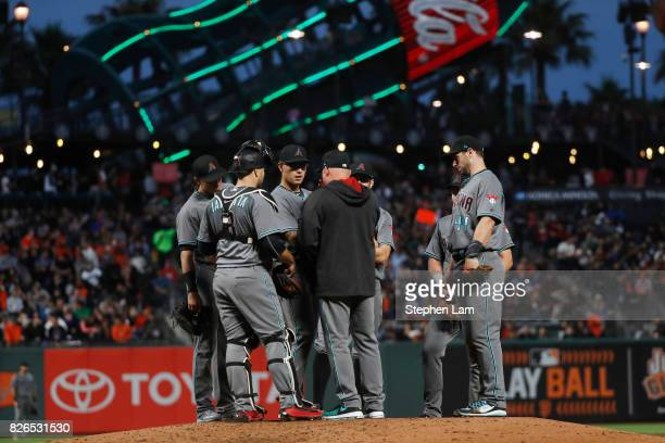 Hitting Coach Mike Butcher of the Arizona Diamondbacks speaks to pitcher Anthony Banda during the fourth inning against the San Francisco Giants at...