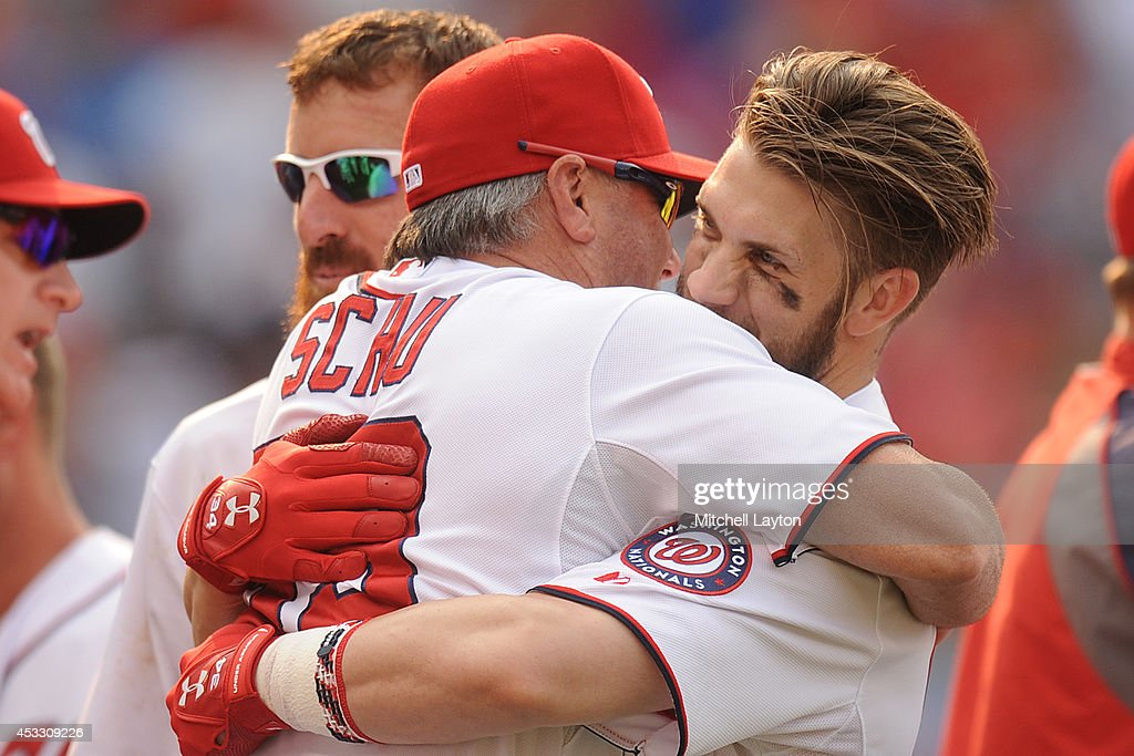 Hitting coach Rick Schu #39 hugs Bryce Harper #34 of the Washington Nationals after hitting a two run walk off home run in the 13th inning during a baseball game against the New York Mets on August 7, 2014 at Nationals Park in Washington, DC. The Nationals won6-3 in the 13th inning.