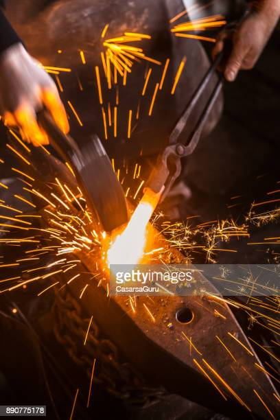 hitting molten iron with a hammer on anvil, with sparks flying - blacksmith shop stock photos and pictures