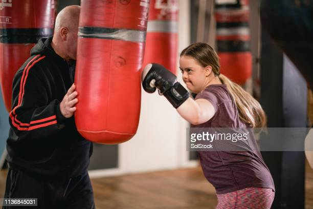 hitting the boxing bag - showus stock pictures, royalty-free photos & images