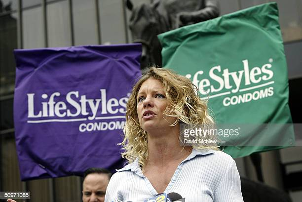 HIVpositive AIDS activist and former Playboy Bunny Rebekka Armstrong speaks to the press in front of banners that look like a giant condoms while...