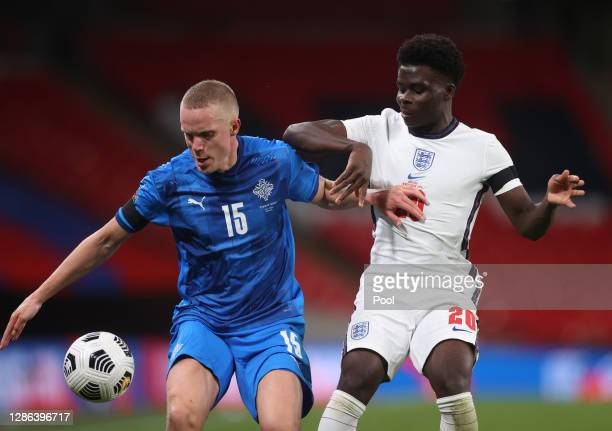 Hjortur Hermannsson of Iceland is challenged by Bukayo Saka of England during the UEFA Nations League group stage match between England and Iceland...