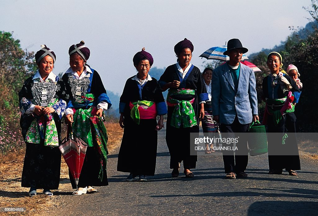 Hmong family in traditionial clothing, in front of their hut, Laos ...