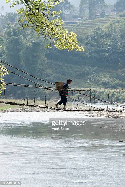 hmong tribesman crossing rope bridge. sapa. vietnam - hugh sitton stock pictures, royalty-free photos & images