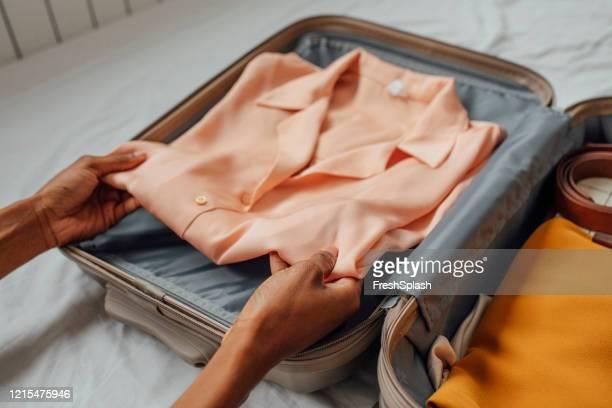hnads de uma mulher anônima embalando suas roupas em uma mala - open blouse - fotografias e filmes do acervo
