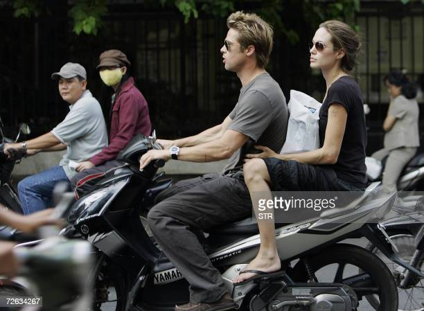 Hollywood movie stars Brad Pitt and his partner Angelina Jolie ride on a motorcycle on a busy street in downtown Ho Chi Minh city 23 November 2006...