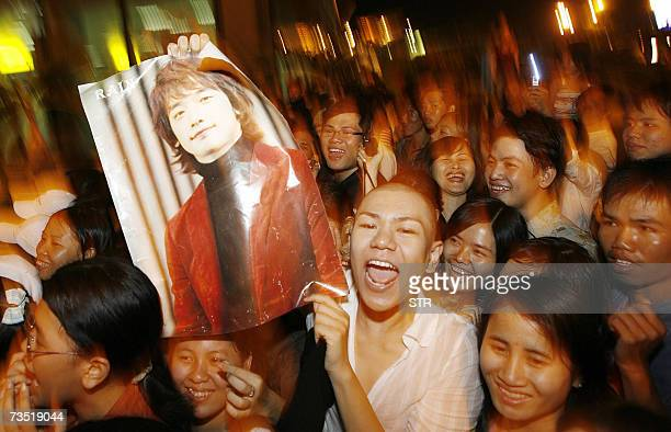 Vietnamese fans cheer up with a posters of South Korean pop star singer and hiphop dancer Jung Jihoon aka Rain as he arrives in Ho Chi Minh city's...