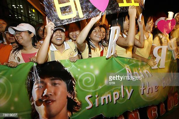 Vietnamese fans cheer up with banners bearing South Korean pop star singer and hiphop dancer Jung Jihoon aka Rain as he arrives in Ho Chi Minh city's...