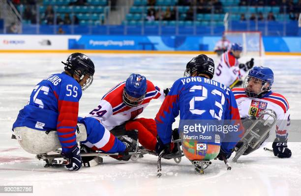 Ho Jong Jang of Korea battles for the puck with Zdenek Safranek of Czech Republic in the Ice Hockey Preliminary Round Group B game between Korea and...