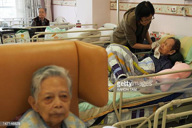 Ho Sze an elderly woman in her late 90s reacts as she has her face cleaned by a family member at an elderly care home in Hong Kong on April 18 2012...