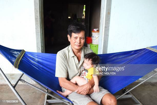 Hoang Lanh, father of 18-year old Hoang Van Tiep who is feared to be among the 39 people found dead in a truck in Britain, cradles his grandchild at...