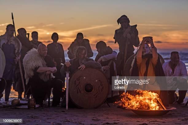 un tesoro de arma blandiendo a sangrientos guerreros vikingos alrededor de una fogata en la noche - ejército de tierra fotografías e imágenes de stock