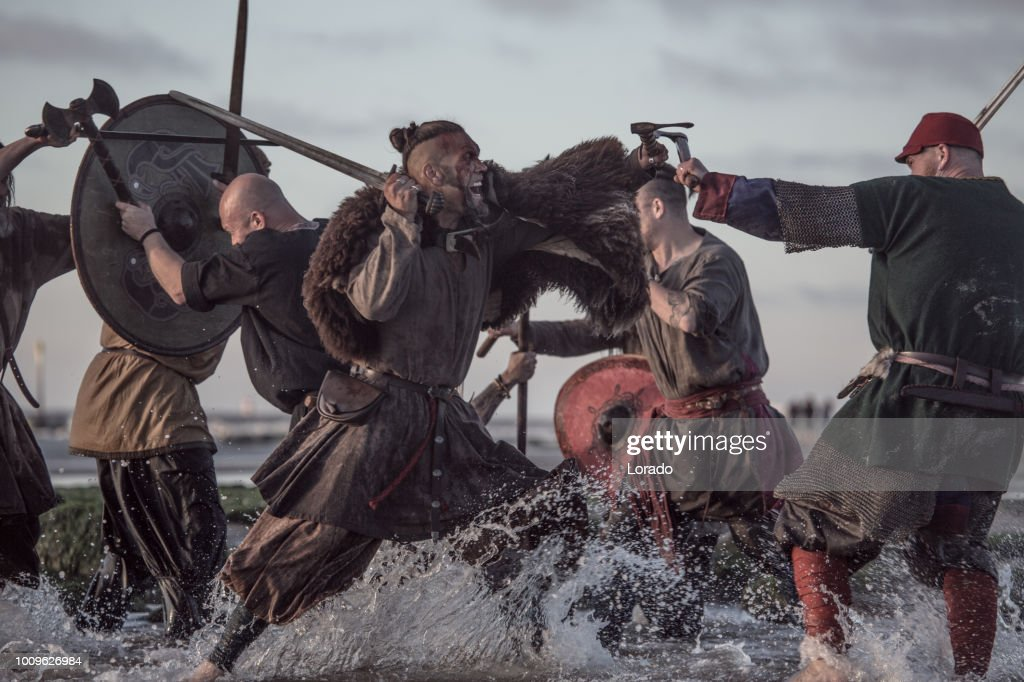 A hoard of Weapon wielding viking warriors fighting in a battlefield scene in the sea : Stock Photo
