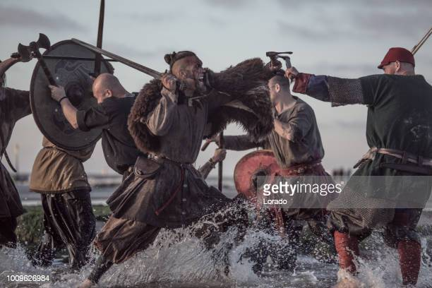 a hoard of weapon wielding viking warriors fighting in a battlefield scene in the sea - reenactment stock photos and pictures