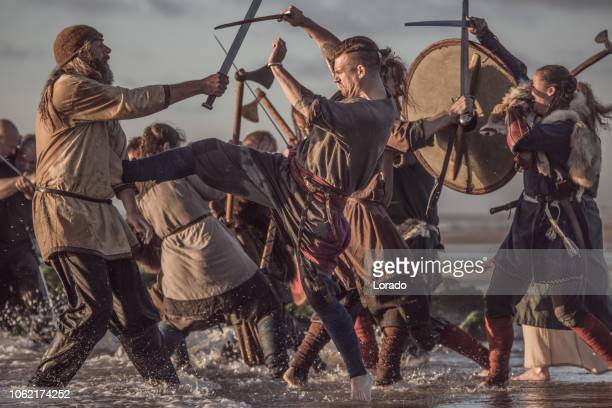 A hoard of Weapon wielding viking warriors fighting in a battlefield scene in the sea