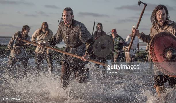 a hoard of weapon wielding viking warriors fighting in a battlefield scene in the sea - medium group of people stock pictures, royalty-free photos & images